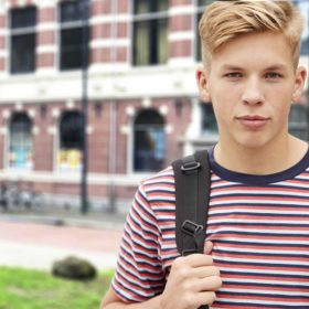 Portrait Of Serious Male High School Student Outside College Building With Other Teenage Students In Background